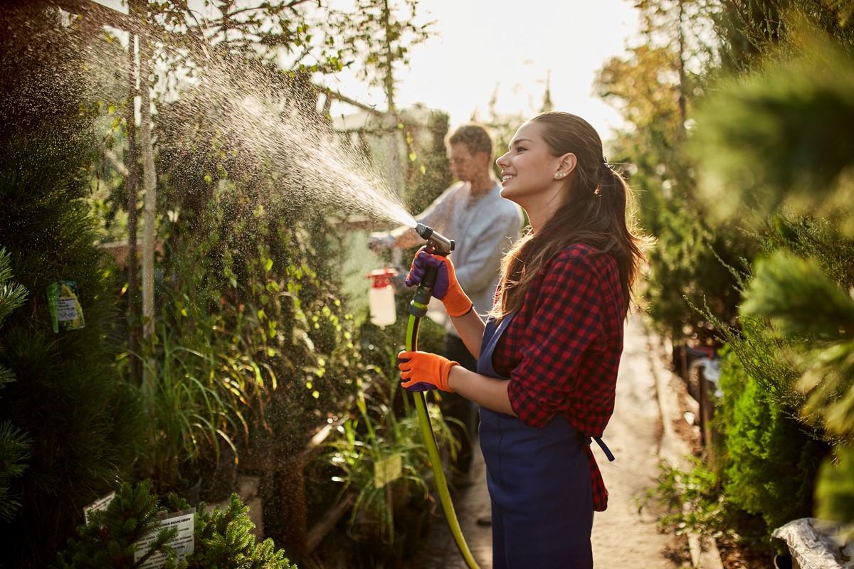 work-in-the-garden-girl-gardener-sprays-water-and-MHBLX5D